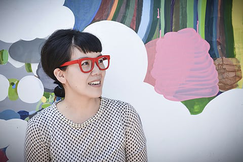 Female student with red-rmmed glasses sits in front of colorful artwork.