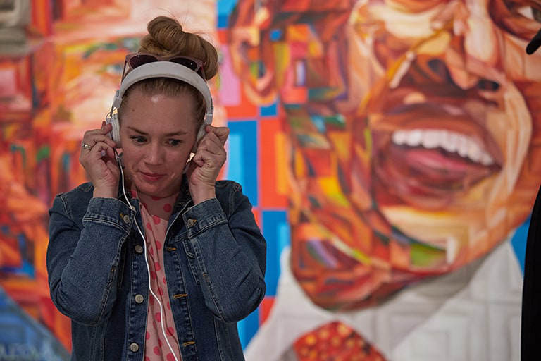 Student listening with headphones at art exhibit