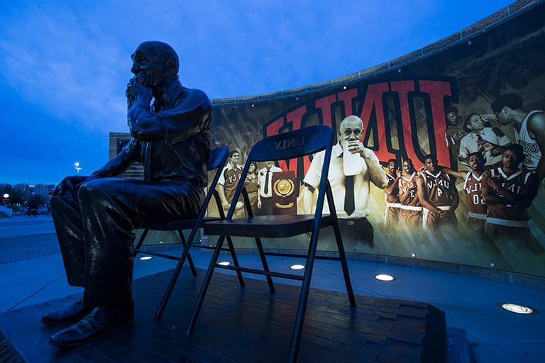 Tarkanian statue at dusk with lighted sign behind