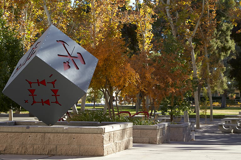 校友 cube sculpture with red markings on each side