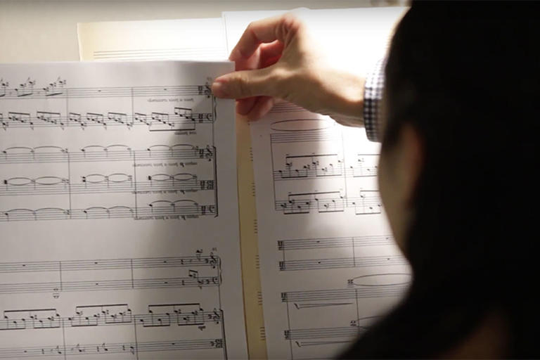 The back of a person's head, as they are holding a piece of sheet music