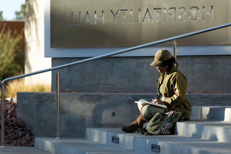 A student studying cultural studies on the stairs leading up to Hospitality Hall.