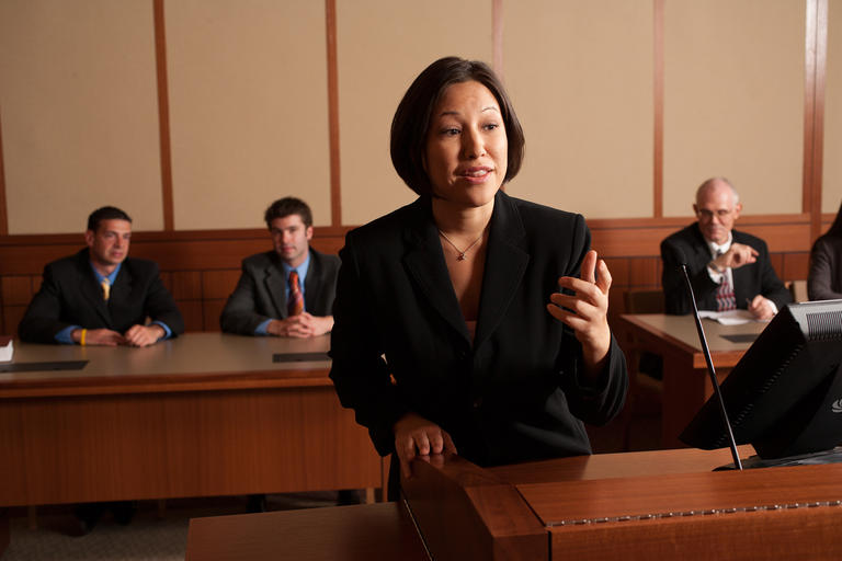 A student participating in a mock trial as peers observe